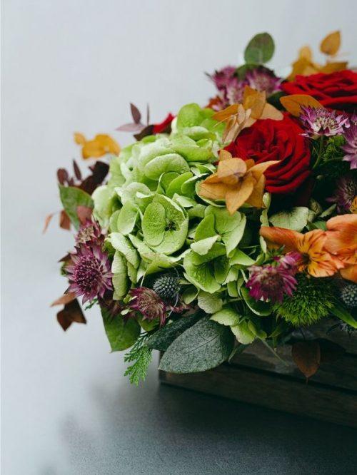 Regala un centro de flores rojas, naranjas y verdes , y recíbelo a domicilio